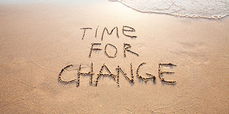 Time for Change written in sand on a beach