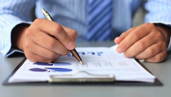 Man reviewing a report with a pen
