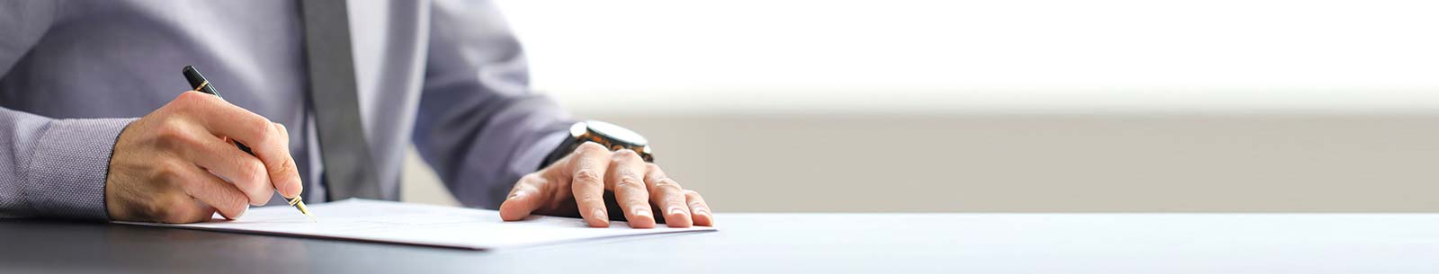 Man holding pen signing document